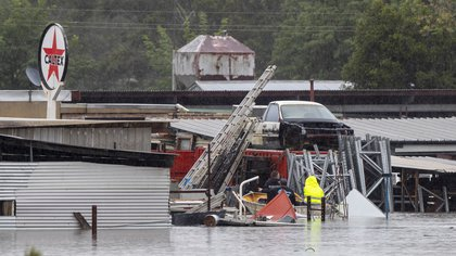 Hombres reman a través de aguas inundadas para inspeccionar edificios sumergidos en Londonderry (AP Photo/Mark Baker)