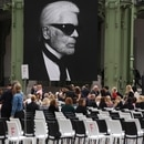 People arrive at the Grand Palais, decorated with photographs picturing late German fashion designer Karl Lagerfeld, at the start of the