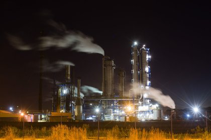Vapors rise from the Total SE petrochemical plant at night in Le Havre, France, on Sunday, Sept. 6, 2020. President Emmanuel Macron's government last week unveiled the long-awaited 100 billion-euro ($118 billion) stimulus plan the French president is betting on to transform the economy and his political fortunes with less than two years to go until elections. Photographer: Nathan Laine/Bloomberg