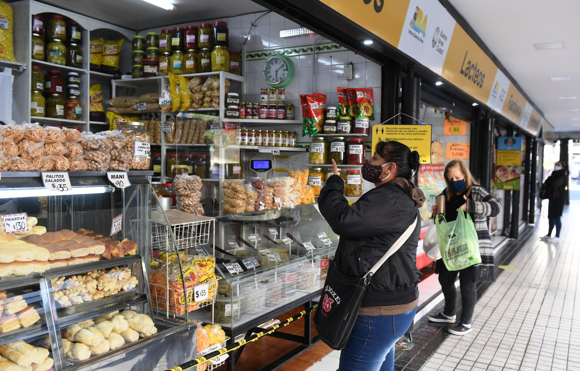 Una vecina del barrio de Caballito mantiene los dos metros de distancia aconsejados mientras una mujer realiza una compra en una de las ferias que tiene el gobierno de la Ciudad