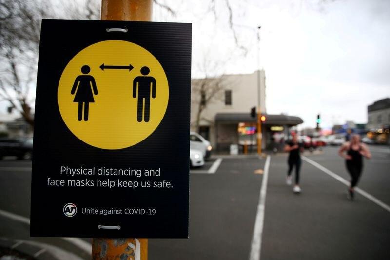 Personas junto a una señal de distanciamiento social contra el coronavirus en Nueva Zelanda (REUTERS/Fiona Goodal)