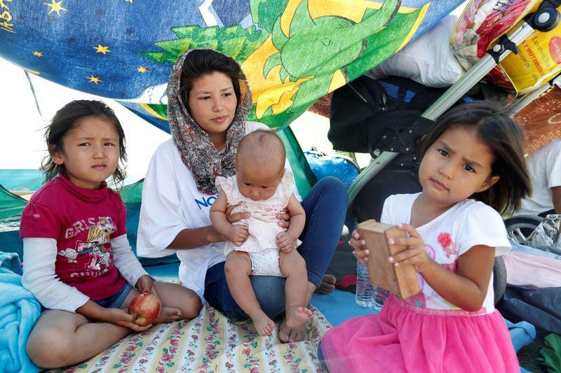 Una mujer afgana sentada junto a sus tres hijas frente a una tienda de campaña en el centro comunitario gestionado por Team Humanity, donde unas 450 personas se han asentado tras el incendio del campamento de Moria, en la isla de Lesbos, Grecia, el 19 de septiembre de 2020. REUTERS/Yara Nardi