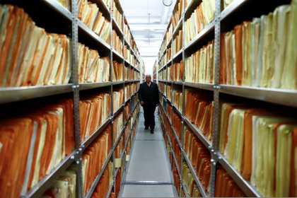 Un miembro del personal de seguridad camina entre estantes que contienen documentos del antiguo Ministerio de Seguridad del Estado de Alemania Oriental (REUTERS/Fabrizio Bensch)