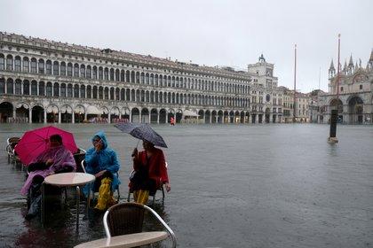 Los turistas se sientan en la Plaza de San Marcos inundada el 12 de noviembre de 2019 (REUTERS/Manuel Silvestri)