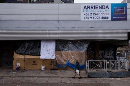 Una mujer camina junto a un campamento improvisado por personas sin techo para resistir la lluvia y el frío del invierno, durante la cuarentena obligatoria por el avance de la COVID-19 en Santiago de Chile