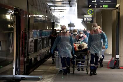 Personal médico traslada a un paciente infectado con el COVID-19 a bordo de un tren de alta velocidad TGV en la estación de tren de Gare d'Austerlitz en París, Francia, el 1 de abril de 2020 (Thomas Samson/Pool vía REUTERS)