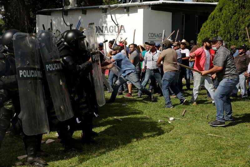 Agricultores chocan con miembros de la Guardia Nacional mexicana durante una protesta contra la decisión del gobierno mexicano de desviar agua de la represa La Boquilla a Estados Unidos, como parte de un tratado bilateral de agua desde 1944 entre ambos países, en Camargo, del estado Chihuahua, Mexico. 8 de septiembre de 2020. REUTERS/Jose Luis Gonzalez
