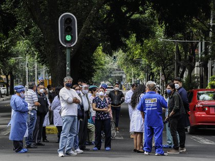 People get to the streets in Mexico City following a quake on June 23, 2020 amid the COVID-19 novel coronavirus pandemic. - A 7.1 magnitude quake was registered Tuesday in the south of Mexico, according to the Mexican National Seismological Service. (Photo by CLAUDIO CRUZ / AFP)