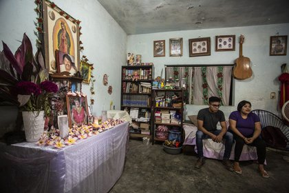 Jesús y Araceli, hijos de Araceli López, junto al altar en honor de su madre, fallecida el 1 de julio de 2020.  (Fotografía: Jacciel Morales)