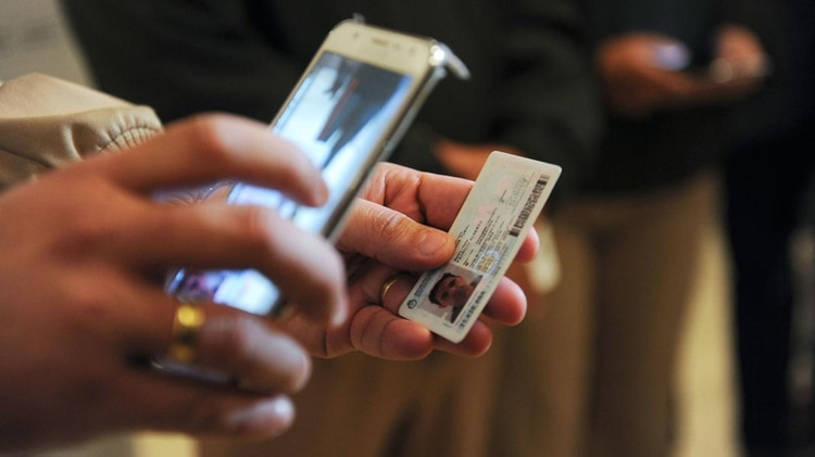 Los efectivos analizan los documentos desde un celular (Télam)