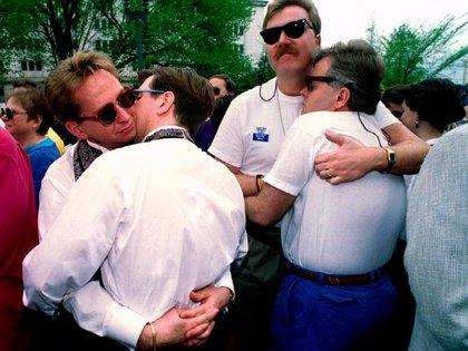 Parejas se abrazan durante una boda masiva el 24 de abril de 1993 frente a la sede del Servicio de Impuestos Internos (IRS) en el centro de Washington. La ceremonia se celebró para protestar por las regulaciones gubernamentales que prohíben el matrimonio entre personas del mismo sexo