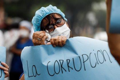 Una mujer del personal de la salud protesta con carteles durante unas manifestaciones para denunciar la falta de medicamentos y recursos para combatir el COVID-19, frente al Hospital de Clínicas en San Lorenzo (Paraguay). EFE/ Nathalia Aguilar
