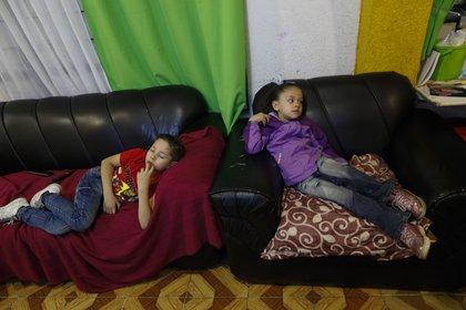 Santi, de 6 años, y su hermana Liz, de 5, luchan por concentrarse en una lección de jardín de infantes televisada mientras los estudiantes regresan a clases pero no a las escuelas en la Ciudad de México, el lunes 24 de agosto de 2020. (Foto AP / Rebecca Blackwell)