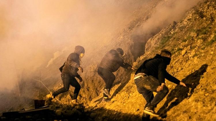 (Guillermo Arias / AFP)Migrantes centroamericanos atravezando la frontera mexicana, desde Tijuana a San Diego durante año nuevo.