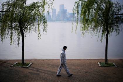 A man wearing protective gear walks by the Yangtze river in Wuhan, Hubei province, as China holds a national mourning for those who died of the coronavirus disease (COVID-19), on the Qingming tomb-sweeping festival, April 4, 2020. REUTERS/Aly Song