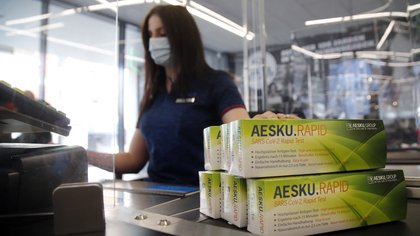 An employee of ALDI Nord poses with Covid-19 rapid tests in one of their stores in Essen, western Germany, on March 05, 2021, amid the novel coronavirus COVID-19 pandemic. - The German discounter Aldi starts to sell Corona rapid tests throughout Germany from February 27, 2021. The sales quantity per customer will be limited to one pack, so that as many customers as possible can benefit, Aldi Nord and Aldi S�d announced on march 5. (Photo by LEON KUEGELER / AFP)
