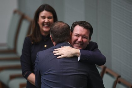Tim Wilson es felicitado por el senadorDean Smith, luego de proponer matrimonio a su pareja.