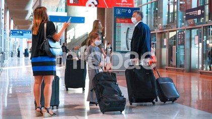 """El ex Presidente escucha las indicaciones una funcionaria diplomática argentina que fue al aeropuerto a asistirlo. """"Fue un viaje largo"""", se excusó ante las preguntas de Infobae (Fotos: Infobae)"""