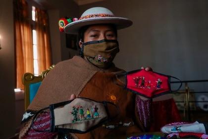 La indígena Ana Alicia Layme, de la comunidad Ayata, muestra tapabocas bordados en La Paz (Bolivia) (EFE/Martín Alipaz)