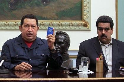 Hugo Chávez juntocon Nicolás Maduro en 2012, con una copia de la constitución bolivariana (AP)