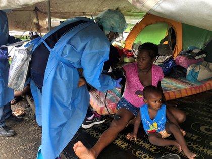 Personal médico examina a un migrante en el campamento de Lajas Blancas, donde los migrantes de África, Cuba y Haití están varados debido a la pandemia de la enfermedad coronavirus (COVID-19), durante una visita de las autoridades panameñas, en la provincia de Darién, Panamá, el 5 de junio de 2020. (REUTERS)