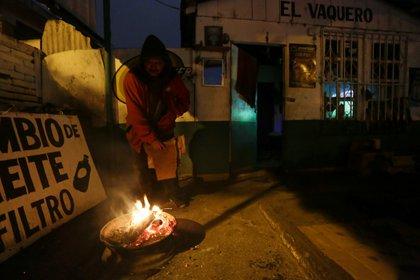 Un hombre se calienta con una fogata durante un frente frío en Matamoros, México 18 de febrero de 2021 (Foto: REUTERS/Daniel Becerril)