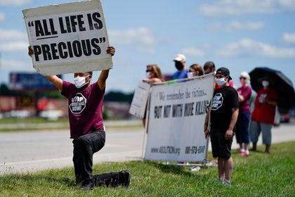 El reverendo Sylvester Edwards se arrodilla mientras otros manifestantes sostienen carteles cerca del Complejo Correccional Federal de Terre Haute, Indiana, para mostrar su oposición a la pena de muerte y la ejecución de Daniel Lewis Lee(Reuters/ Bryan Woolston)