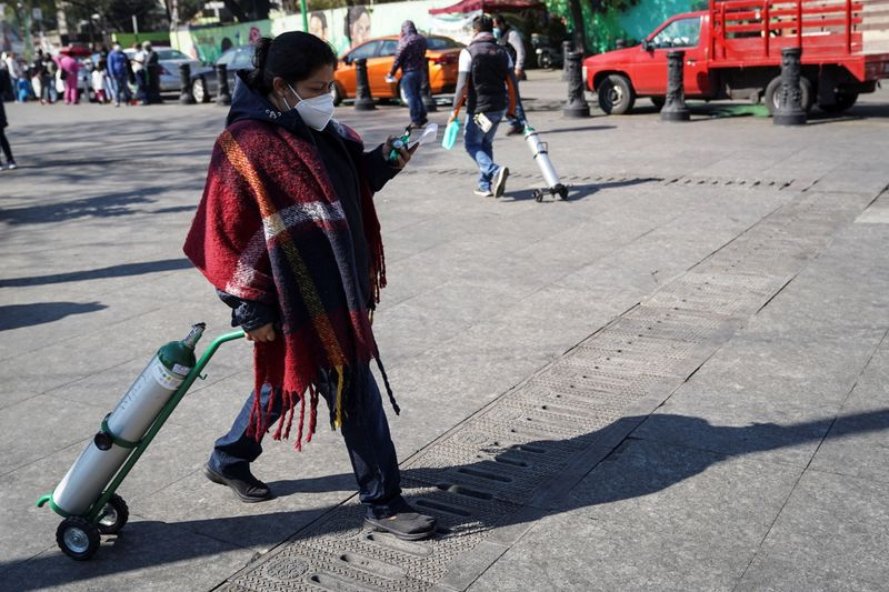 Villagers carry oxygen tanks for their relatives who are sick with COVID-19, as part of the free recharge program of the government of Mexico City, in the municipality of Iztapalapa. Mexico, January 18, 2021.
