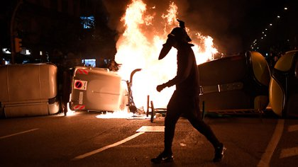Un manifestante pasa junto a contenedores de basura en llamas durante los enfrentamientos con los Mossos d'Esquadra tras una protesta contra el encarcelamiento del rapero Pablo Hasél en Barcelona el 19 de febrero de 2021 (Foto de Pau BARRENA / AFP)