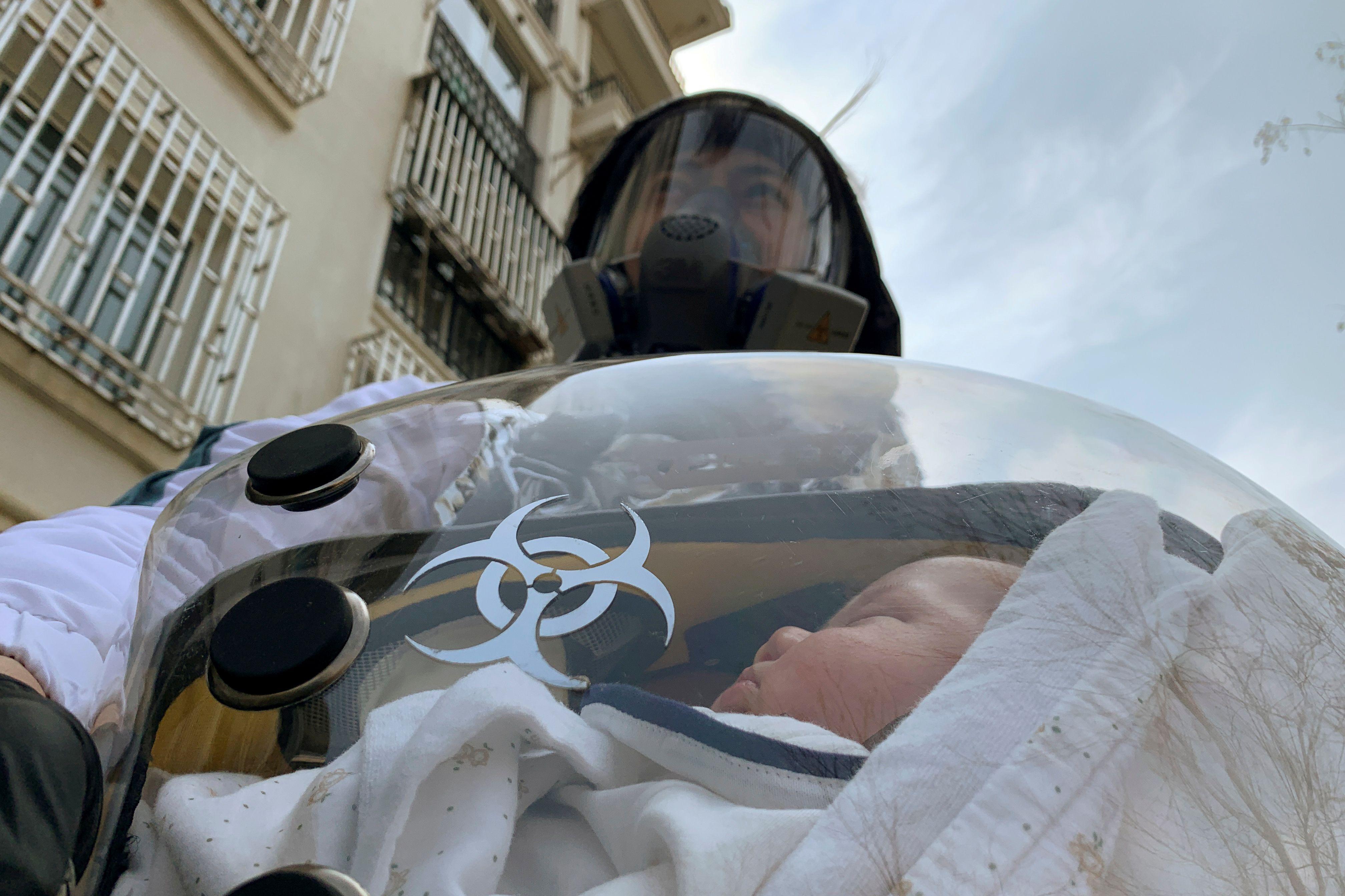 Un hombre carga a su bebé de dos meses con trajes de protección (Reuters)