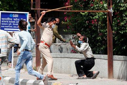 Un policía indio aplica castigos físicos a un hombre que, según las autoridades, había quebrado las normas de distanciamiento social en Nueva Delhi (Reuters)