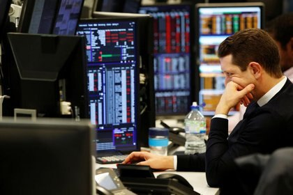 FILE PHOTO: Traders work at their desks whilst screens show market data at CMC Markets in London, Britain, January 16, 2019. REUTERS/John Sibley