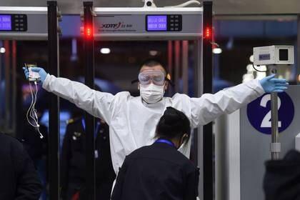 Un hombre con equipo de protección pasa por un control de seguridad en la estación de tren de Wuchang antes de que se levanten las restricciones de viaje para salir de Wuhan, la capital de la provincia de Hubei y el epicentro del brote de la nueva enfermedad coronavirus de China (COVID-19), el 7 de abril de 2020. Foto tomada el 7 de abril de 2020. REUTERS/Stringer