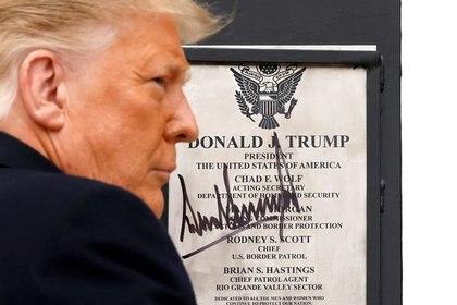 El presidente de Estados Unidos, Donald Trump, firma una placa colocada en el muro de la frontera entre Estados Unidos y México durante su visita, en El Álamo, Texas, Estados Unidos. 12 de enero de 2021. REUTERS/Carlos Barría