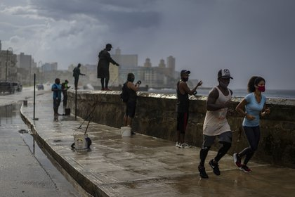 Una pareja con máscaras contra la propagación del nuevo coronavirus trota bajo la lluvia, pasando frente a hombres pescando en el malecón, en La Habana, Cuba, el martes 6 de octubre de 2020. (AP Photo / Ramon Espinosa)