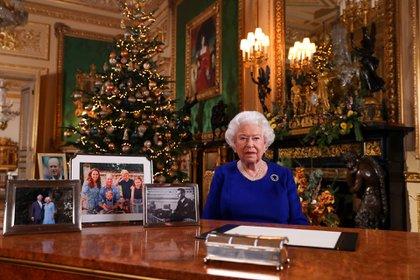 Una imagen publicada el 24 de diciembre de 2019 muestra a la reina Isabel II de Gran Bretaña posando para una fotografía después de grabar su mensaje anual del día de Navidad, en el Castillo de Windsor, al oeste de Londres. En su escritorio no hay rastros de Meghan Markle y del príncipe Harry (AFP)