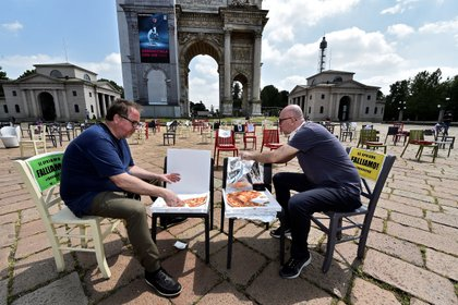 """Los restauradores Savino Tolentino y Paolo Polli comen pizza mientras se sientan en medio de sillas vacías frente al Arco della Pace, como parte de una protesta para exigir más ayuda del gobierno, luego del brote de la enfermedad del coronavirus (COVID-19), en Milán. Los letreros decían: """"¡Si abrimos, quebramos!"""" (REUTERS / Flavio Lo Scalzo)"""