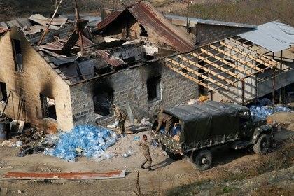 Soldados armenios cargan botellas con agua en el camión junto a una casa quemada en la aldea de Knaravan