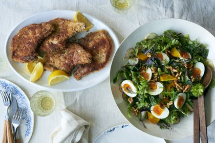 Pan-fried breaded pork chops and a spring salad with sweet herbs, egg and walnuts, in New York, March 23, 2021. For his birthday, David Tanis is making what he craves: a special salad, breaded pork chops, and comforting baba au rhum. Food styled by Simon Andrews. (David Malosh/The New York Times)
