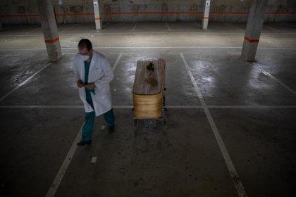 El director de una funeraria camina junto al ataúd de la última víctima del COVID-19 almacenado en un aparcamiento subterráneo convertido en morgue, en Barcelona, España, el domingo 17 de mayo de 2020 (Foto AP/Emilio Morenatti)