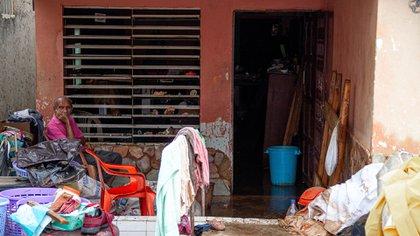 Un hombre permanece sentado fuera de su casa junto a sus enceres dañados y mojados por las fuertes lluvias (EFE/ Henry Chirinos)