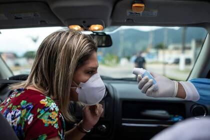 Un trabajador de la salud controla la temperatura de una mujer dentro de su auto en una barrera sanitaria desplegada en San Sebastián, en el estado de San Pablo, Brasil. La economía regional será una de las más castigadas por el paso del coronavirus (Reuters)