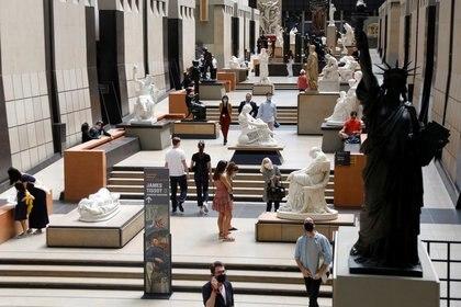 Visitantes usan mascarillas mientras miran obras de arte durante en una visita al Museo de Orsay, en la antigua estación de tren Gare d'Orsay, luego de reabrir sus puertas al público después de las medidas tomadas por el coronavirus en París, Francia. 23 de junio de 2020. REUTERS/Charles Platiau