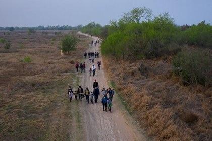Familias solicitantes de asilo y menores no acompañados de América Central caminan hacia el muro fronterizo después de cruzar el río Grande hacia Estados Unidos desde México en una balsa, en Penitas, Texas, EEUU