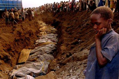 Una niña refugiada contempla una fosa común donde fueron enterrados decenas de cuerpos el 20 de julio de 1994 (Reuters)