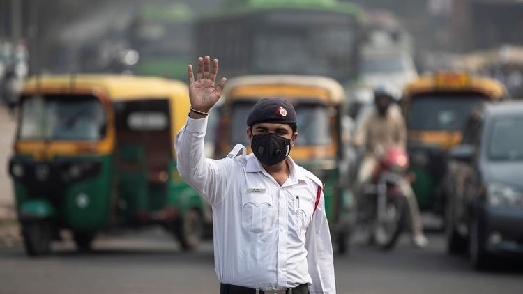 Un policía de tránsito vigila el cumplimiento de las restricciones, protegido con una mascarilla (Reuters)