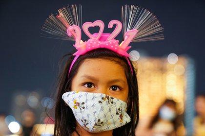 Una niña con mascarilla espera la llegada del 2021 en Bangkok, Tailandia (Reuters/ Athit Perawongmetha)