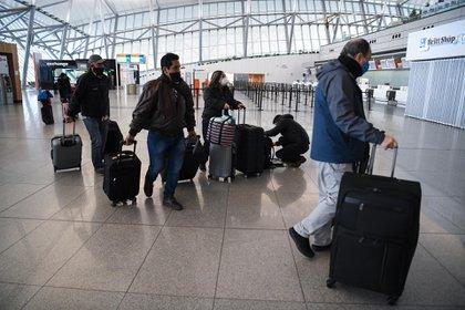 Personas en el aeropuerto de Montevideo. (AFP)