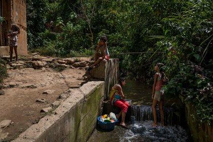 Un grupo de personas en una quebrada de agua (EFE/ Miguel Gutiérrez)