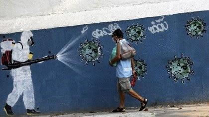 Un hombre camina junto a un grafiti que muestra a un limpiador con equipo de protección rociando virus con la cara del presidente de Brasil Jair Bolsonaro, en medio del brote de la enfermedad coronavirus (COVID-19), en Río de Janeiro, Brasil. 7 de octubre de 2020. REUTERS/Ricardo Moraes